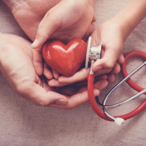 child and adult holding red heart with stethoscope, heart health